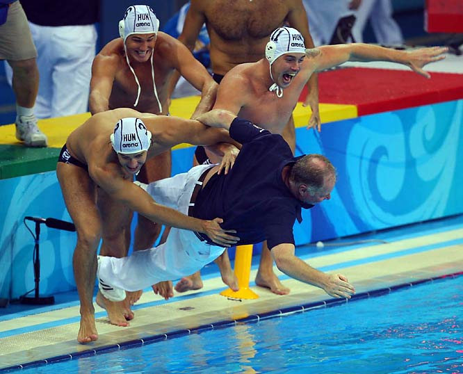 Hungary's head coach Denes Kemeny gets thrown into the pool by Norbert Madaras (left), Norbert Hosnyanszky (top) and Gabor Kis after beating the U.S. for gold in water polo.