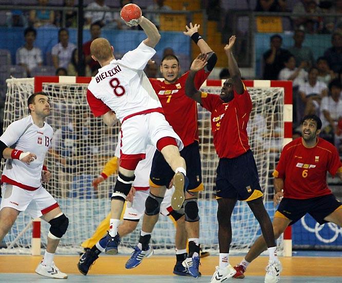 Poland's Karol Bielecki attempts to score against Spain in theteam handball preliminaries.
