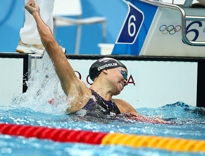Natalie Coughlin celebrates after winning gold in the 100m backstroke, becoming the first woman to ever defend her title in the event. .