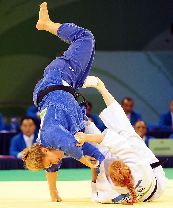 Ronda Rousey of the U.S. (blue) takes a tumble while taking on Germany's Annett Boehm in judo.