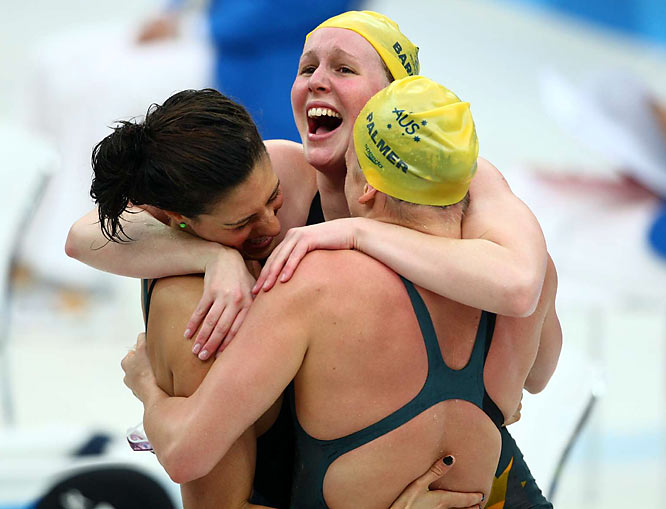 Australia's Bronte Barratt (center) hugs Stephanie Rice (left) and Kylie Palmer after winning gold and setting a new world record in the 4 x 200m freestyle relay with a time of 7:44.31.