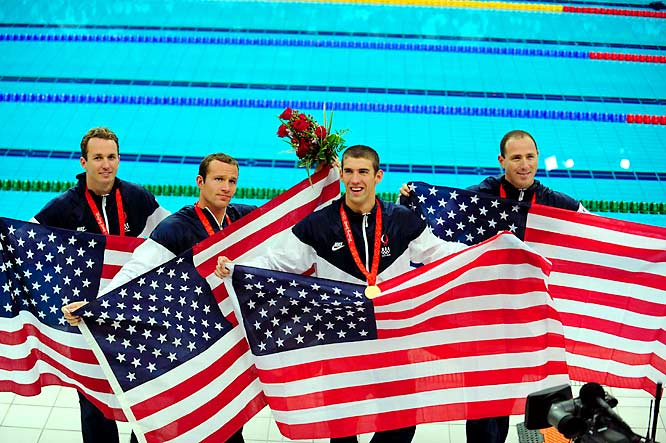 (Left to right) Medalists Aaron Peirsol, Brendan Hansen, Michael Phelps, and Jason Lezak each hold their own American Flag after winning the gold medal with a world record of 3:29.34.
