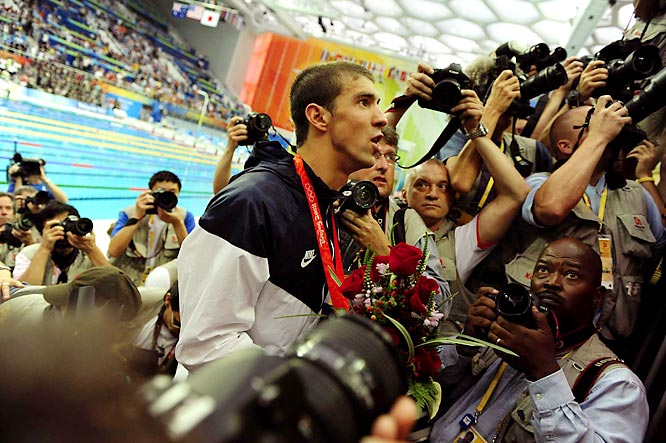 Michael Phelps climbs through a horde of photographers to bring flowers to his mother, Debbie, and two sisters.