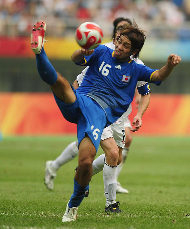 Japan's Takuya Honda keeps the ball away from a U.S. player.