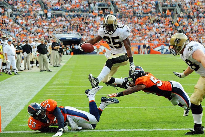 Reggie Bush hurdles over Marquand Manuel (33) and Nate Webster (58) for a third quarter touchdown.  Bush had 178 all-purpose yards and two TDs in the Saints 34-32 loss to the Broncos.