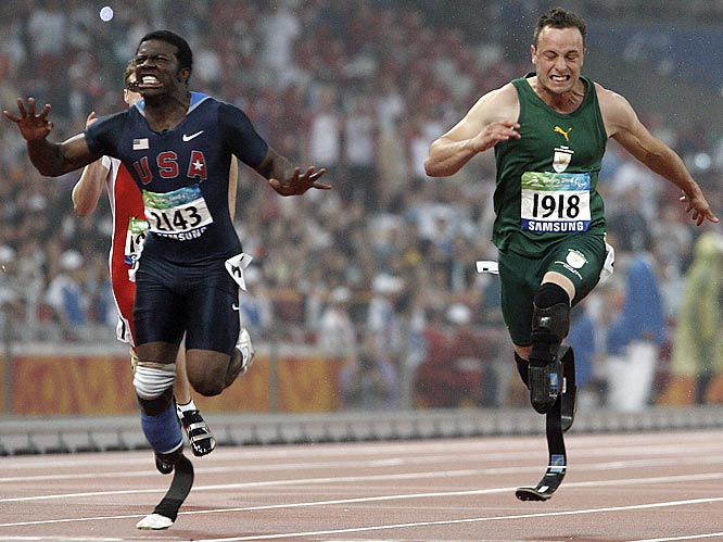Oscar Pistorius of South Africa, right, crosses the finish line ahead of Jerome Singleton of the U.S. in the 100.