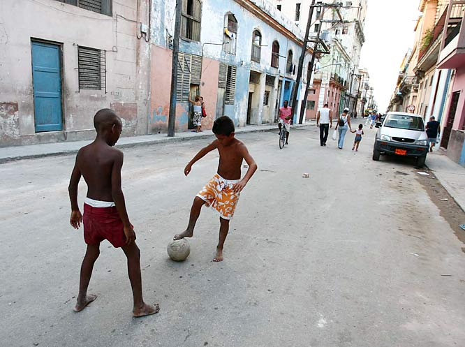 Two barefoot kids go one-on-one with a futbol.