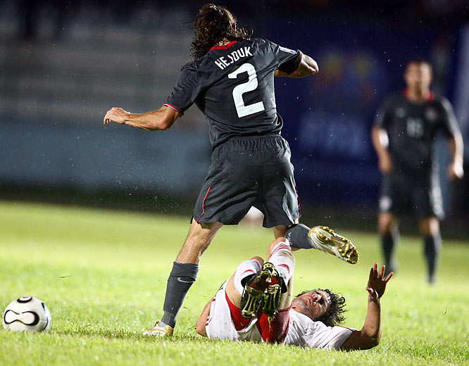 Frank Hejduk steps over Cuba's Jorge Clavelo.