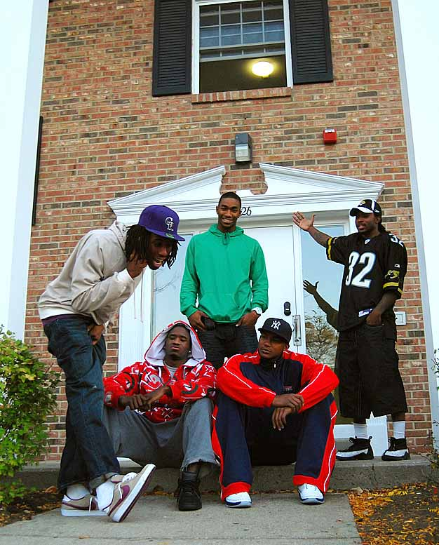 """Dayton hoopsters Marcus Johnson and London Warren (standing in back) welcome you to their crib. Teammates Rob Lowery, Mickey Perry and Chris Wright stop by to say """"hey"""" now and then. On the court, these guys are serious. But off the court, they goof around as much as anybody."""