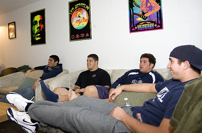 The players laugh as they watch some television together.  Oakley (second from right) does not find this nearly as amusing as his teammates.