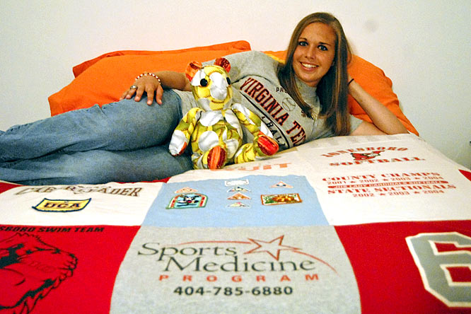 Lowry and her stuffed animal relax on the quilt her mother crafted out of old t-shirts and patches.