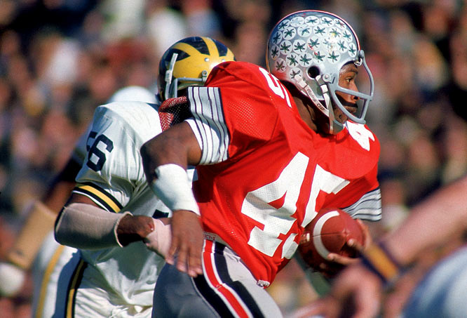 "Even if Tim Tebow can do it this year, winning two Heisman's won't be an original feat:  Ohio State's Archie Griffin won the award the first time in 1974 as he picked up 111 yards in a 12-10 win over Michigan that sent the Buckeyes to their third straight Rose Bowl.  He did it again in 1975, when Woody Hayes told SI ""The greatest back I've ever seen or coached ... He's also the most popular player we've ever had, by far."""