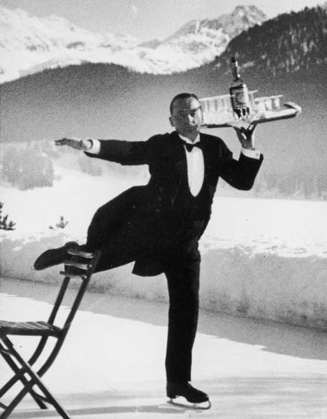 """Among the earliest of Alfred Eisenstaedt's renowned images is this one, made at the ice rink of the legendary Grand Hotel in St. Moritz, Switzerland. """"I did one smashing picture of the skating headwaiter,"""" Eisenstaedt recalled later. """"To be sure the picture was sharp, I put a chair on the ice and asked the waiter to skate by it. I had a Miroflex camera and focused on the chair."""""""