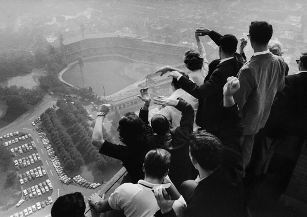 """When recalling the 1960 World Series, in which the Pittsburgh Pirates beat the New York Yankees four games to three to claim their first title in 35 years, many fans bring up Chuck Thompson's radio call of the final play: baseball's first-ever series-ending home run. """"There's a swing and a high fly ball going deep to left, this may do it! . . . Over the fence, home run, the Pirates win! Ladies and gentleman, Bill Mazeroski has just hit a one-nothing pitch over the left-field wall to win the 1960 World Series!"""" The classic photograph to emerge from that series wasn't even taken in the ballpark, but from atop the Cathedral of Learning at the University of Pittsburgh, where students got a bird's-eye view of the action and George Silk got an altogether unique sports photo."""