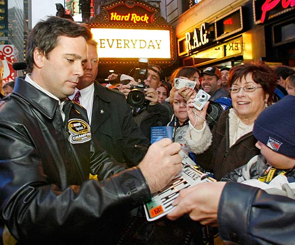 Cup champion Jimmie Johnson signs autographs in New York's Times Square on his way to a party at the Hard Rock.
