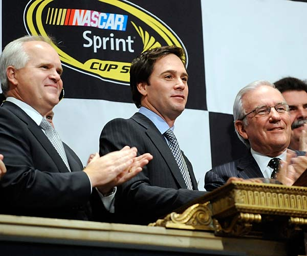 The NASCAR champ is applauded by Lowes CEO Robert Niblock, left, and Sprint CFO Bob Brust, as he rings the New York Stock Exchange opening bell.  Before Johnson began the day, traders crowded him to get an autograph.