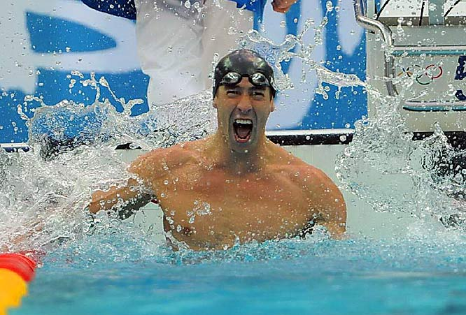 Michael Phelps celebrates winning the gold medal in an Olympic-record time of 50.58 and by 0.01. It was his seventh gold medal at the Beijing Games.