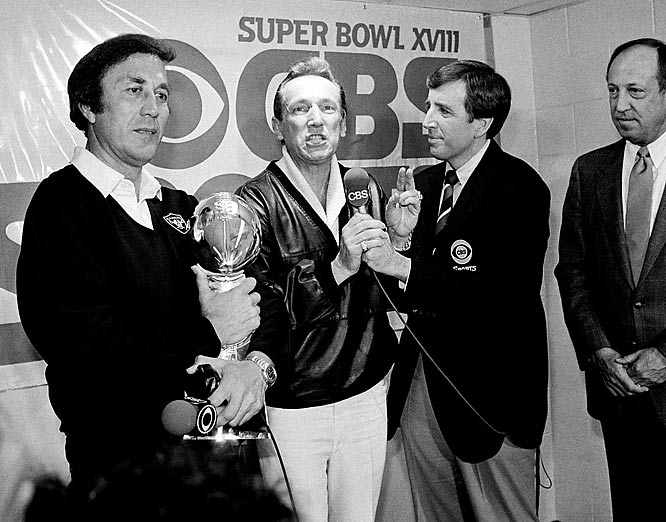 Los Angeles Raiders coach Tom Flores clutches the Super Bowl trophy as Raiders managing general partner Al Davis is interviewed by Brent Musburger in the locker room after the Raiders' 38-9 win over the Washington Redskins in Super Bowl XVIII.  At right is NFL Commissioner Pete Rozelle.