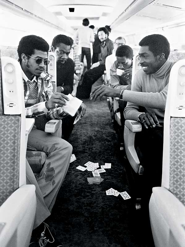 Dean Meminger (left) and Earl Monroe (right)  enjoy a game of cards on their charter plane back to New York after beating Los Angeles for the championship.