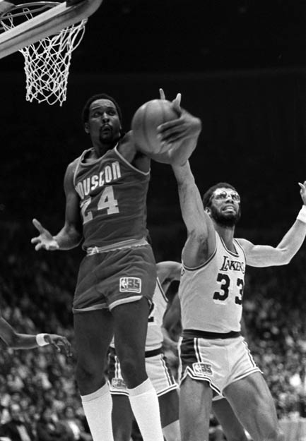 Houston Rockets center Moses Malone grabs an NBA-record 21 offensive rebounds in a 117-100 victory over Seattle.