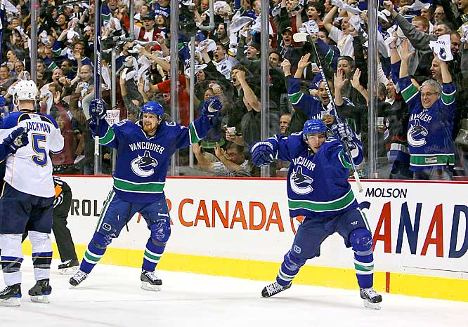 Canucks forwards Daniel Sedin (left) and Alexandre Burrows celebrate Burrows' goal against the Blues during Game 2 of their quarterfinal playoff matchup.