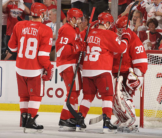 Chris Osgood (right) made made 22 saves for his 15th playoff shutout.