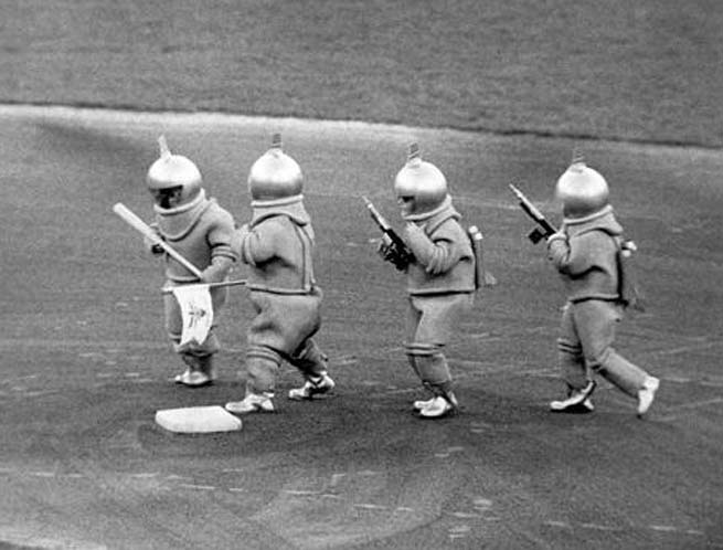 "In another of Bill Veeck's publicity stunts, 3-foot-7 Eddie Gaedel returns to a major league field along with three other little people. Arriving by helicopter and dressed as Martians, the quartet shake hands with Nellie Fox and Luis Aparicio near second base on Comiskey Park's infield and give them toy ray guns to help Fox and Aparicio ""in their struggle with giant earthlings."""
