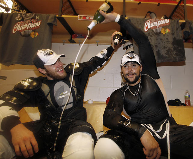 Chicago Blackhawks defenseman Jordan Hendry (left) and right wing Dustin Byfuglien pour champagne onto each other in the locker room after the Blackhawks won the Stanley Cup with an overtime goal in Game 6.