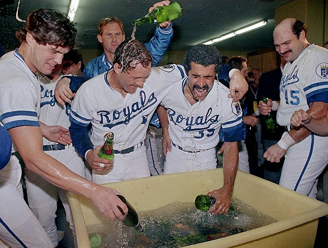 George Brett (center, left) and teammates get cold champagne from a tub in the Royals locker room to celebrate after their World Series win over the St. Louis Cardinals.