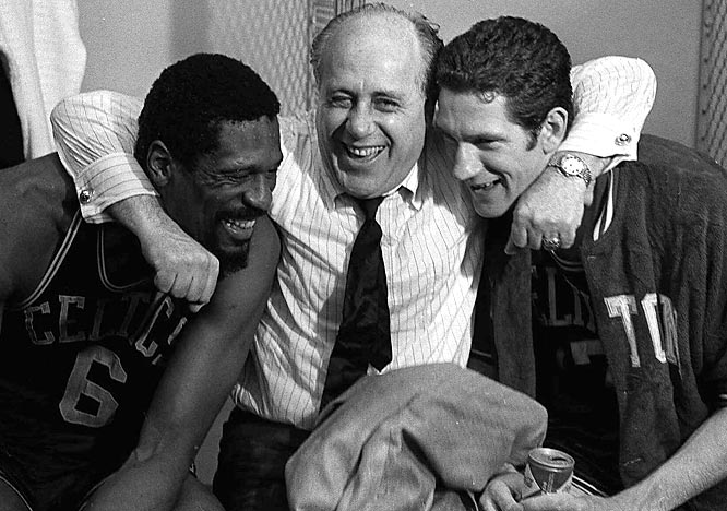 Boston Celtics general manager Red Auerbach hugs Bill Russell and John Havlicek after defeating the Los Angeles Lakers to win the NBA Championship.