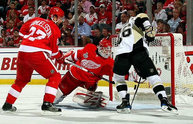 Red Wings' Goalie Chris Osgood snags the puck, keeping it away from Pittsburgh's Ruslan Fedotenko during Game 5 of the Stanley Cup finals. Osgood had 22 saves in Detroit's 5-0 win. The home-ice victory put the Red Wings one game away from their second straight Stanley Cup title.