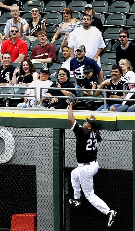 White Sox right fielder Jermaine Dye climbs the right field wall and robs Tigers DH Marcus Thames of a home run during the second inning in the first game of a doubleheader.