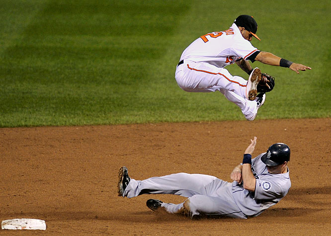 Oriole's shortstop Robert Andino leap frogs Seattle's Russell Branyan after throwing to first to complete the double play on a Adrian Beltre ground ball in the sixth. Baltimore beat Seattle 3-1, snapping a five-game losing streak that included two losses to the Mariners the previous week.