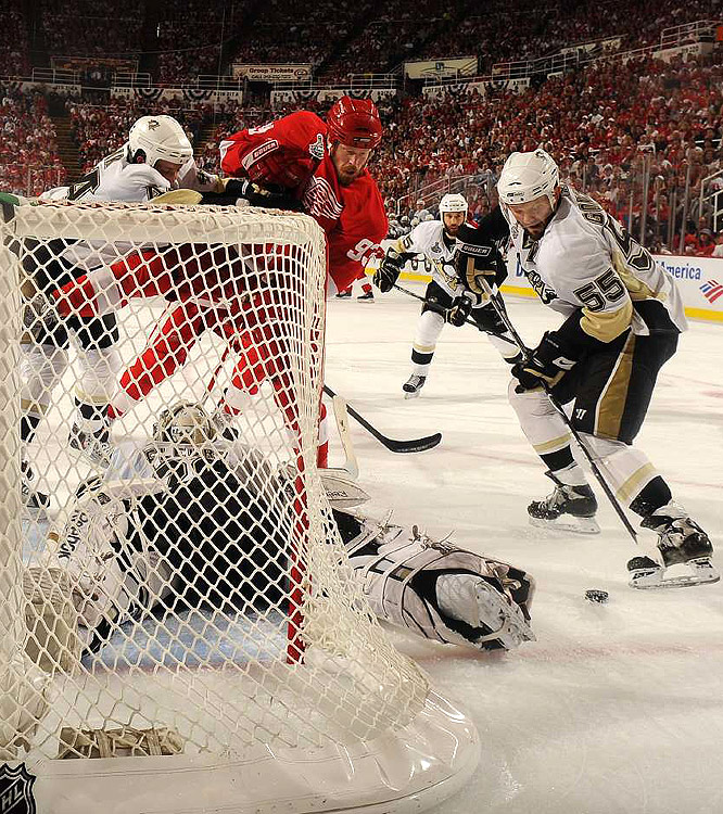 With Pittsburgh goalie Marc-Andre Fluery flat on his stomach and Detroit winger Johan Franzen (93) bearing down, defenseman Sergei Gonchar (55) helped keep the puck out of the net.