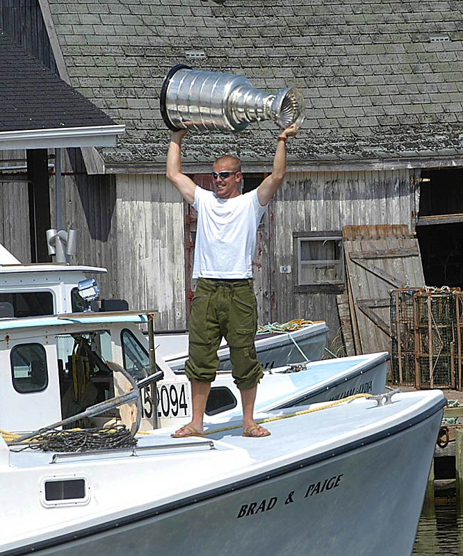 Tampa Bay center Brad Richards, who led the Lightning to the 2004 championship, hoists the Stanley Cup over his head as he and family members take a cruise on his father's lobster boat in Murray Harbour, P.E.I.