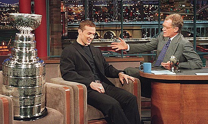 "Detroit Red Wings captain Steve Yzerman sits next to his his team's 1998 Stanley Cup during an appearance on the ""Late Show with David Letterman."""