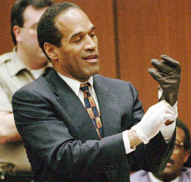 During the O.J. Simpson murder trial, Simpson is asked to put on a pair of gloves. The gloves are said to have been worn by the killer on the night of the murders of Nicole Brown and Ronald Goldman, but do not appear to fit the former NFL great.