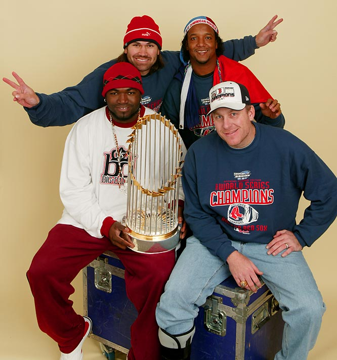"""David Ortiz, Johnny Damon, Pedro Martinez and Curt Schilling pose with the World Series trophy. The quartet helped the Red Sox shed the 86-year-old """"curse"""" and win the franchise's first World Series since 1918."""