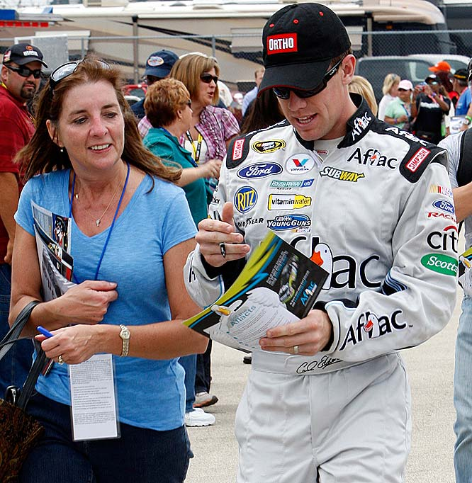 Carl Edwards signs an autograph for a fan during practice for the NASCAR LifeLock 400.