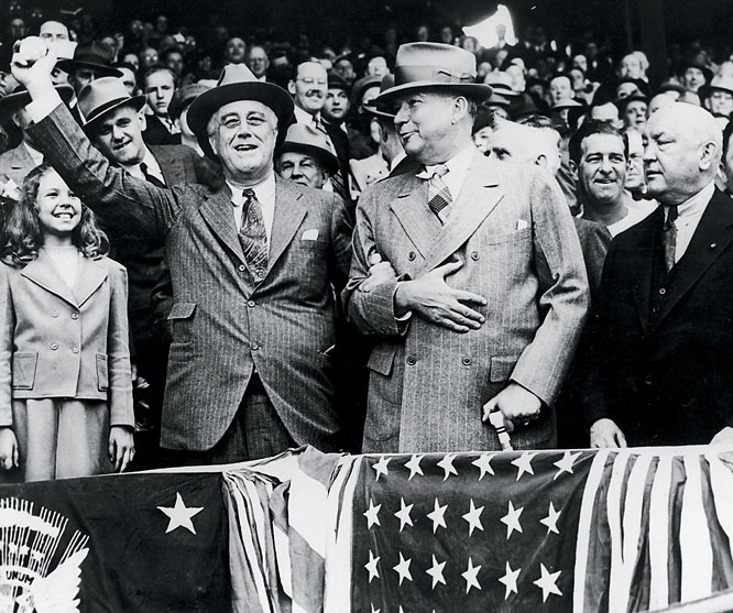 Franklin D. Roosevelt prepares to throw the first ball of the 1941 baseball season while gripping the arm of his Presidential Secretary, General Edwin M. Watson, for support in the stands of Griffin Stadium in Jacksonville, Fla.