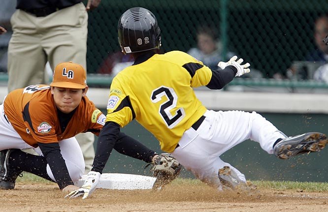 Claycandy Hariquez is tagged out at third by Yobel Pozo of Venezuela.