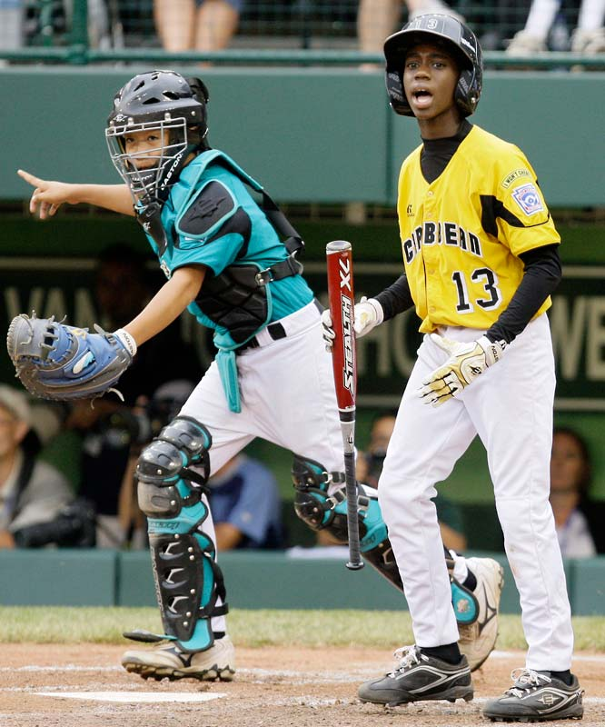 Taoyuan,Taiwan catcher Yu Chieh Kao, left, begins to celebrate after Willemstad, Curacao's Richendly Bicentini (13) strikes out to end an international semifinal game.  Taiwan won 5-2.