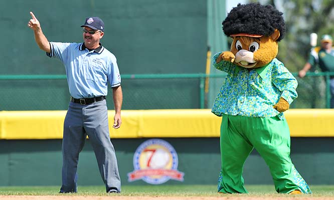Dugout, the mascot of Little League Baseball, shares a light moment with an umpire during a break in the action.