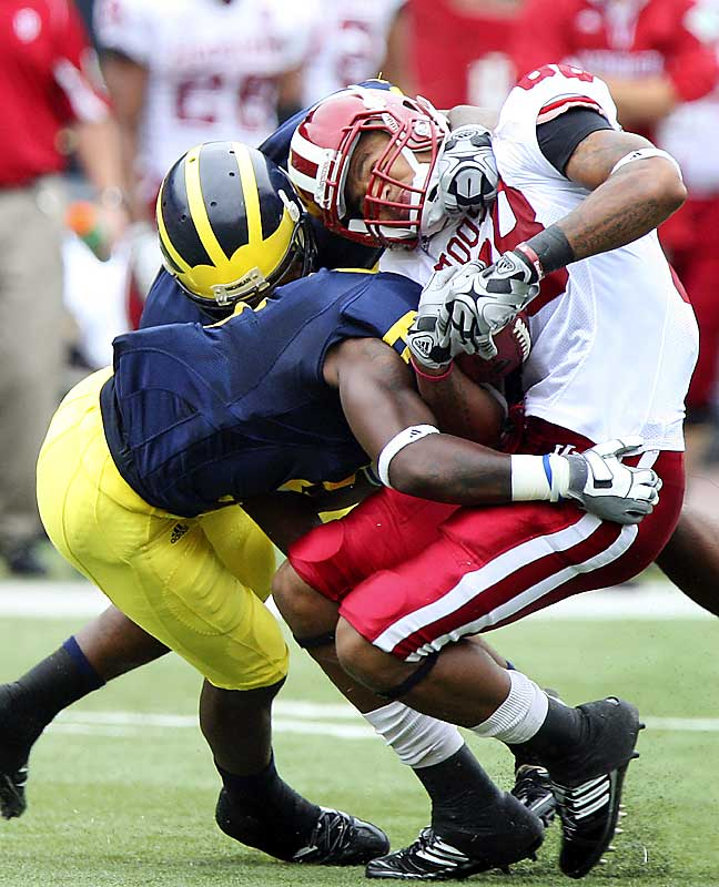 Michigan cornerback Donovan Warren, foreground, and linebacker Obi Ezeh put the squeeze on receiver Damarlo Belcher, but the undefeated Wolverines had a hard time putting away the Hoosiers. An 85-yard run by Darius Willis put Indiana up 33-29 with less than nine minutes remaining. Freshman QB Tate Forcier led the Wolverines back, throwing his second TD of the day with 2:29 to go.