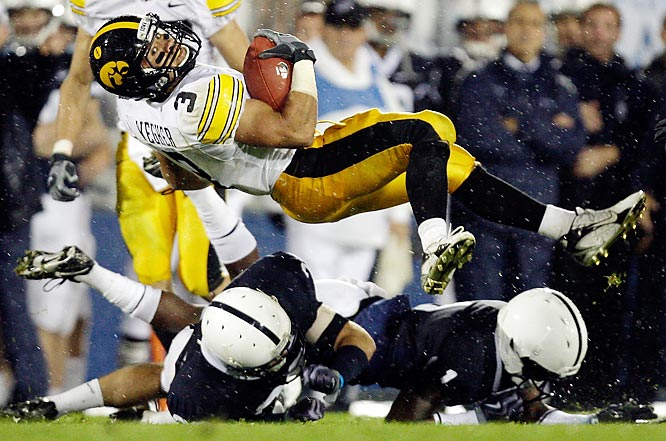 Iowa running back Brandon Wegher flips over Penn State defenders Drew Anderson, left, and A.J. Wallace during the second half of an NCAA college football game, Saturday, Sept. 26, 2009, in State College, Pa. Iowa won 21-10.