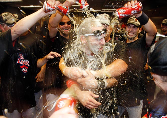 St. Louis Cardinals third baseman Mark DeRosa (7) is doused by teammates after they beat the Colorado Rockies 6-3 to capture the National League Central division title following a baseball game on Saturday, Sept. 26, 2009, in Denver.