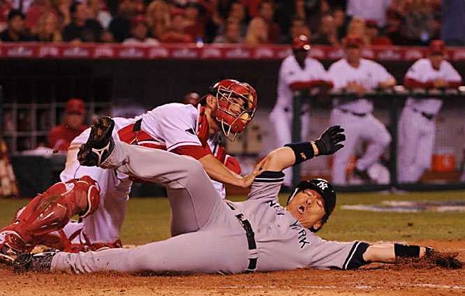 Hideki Matsui scores past catcher Jeff Mathis on a Robinson Cano triple in the seventh inning.