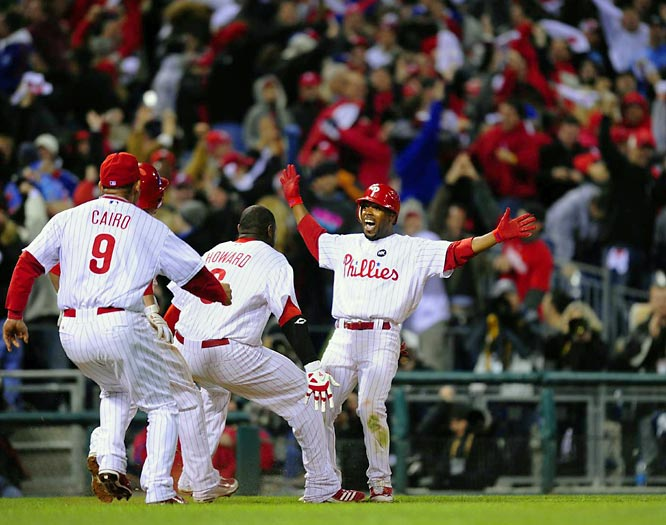 Jimmy Rollins reacts to teammates rushing to him along the third base line after his clutch hit to win the game and give the Phillies a 3-1 series lead.