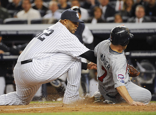 Yankee pitcher CC Sabathia misses the tag after a passed ball, allowing Joe Mauer to score in the third inning.