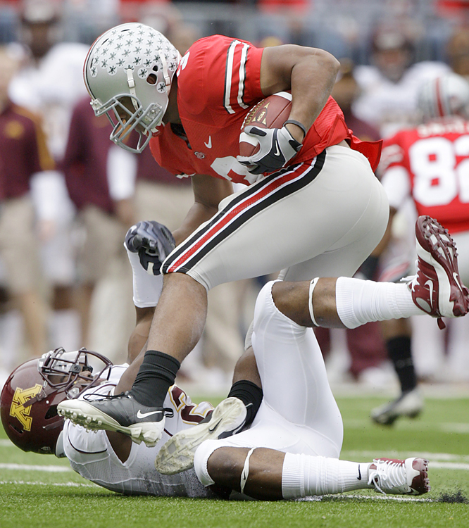 Ohio State's Brandon Saine (right) runs over Minnesota's Simoni Lawrence early in their Big Ten game. Terrelle Pryor threw for 239 yards and rushed for 104 more as the Buckeyes, who amassed 509 yards of total offense, outscored the Gophers 31-7 in the second half.